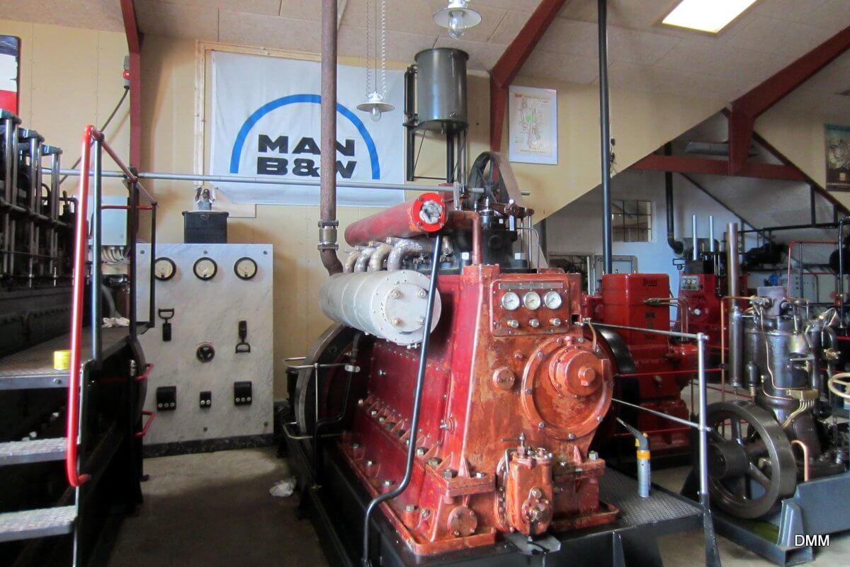 Over motoren er monteret et par lamper, som er viser belysningen i en maskinstue fra den tid motoren var i aktiv tjeneste.